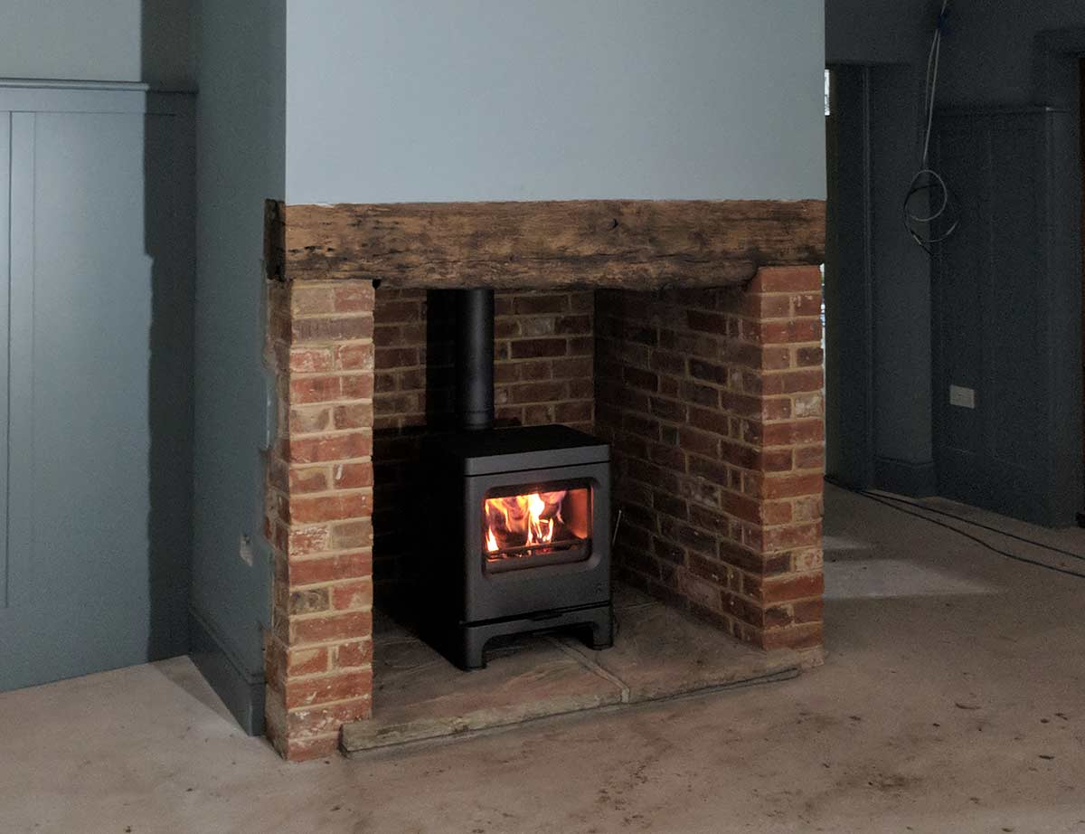red brick fireplace with charnwood stove
