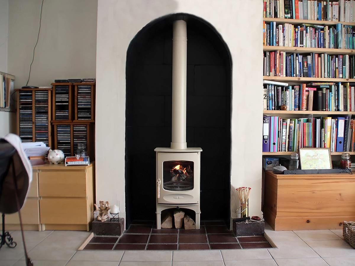 Almond C four stove in arched fireplace