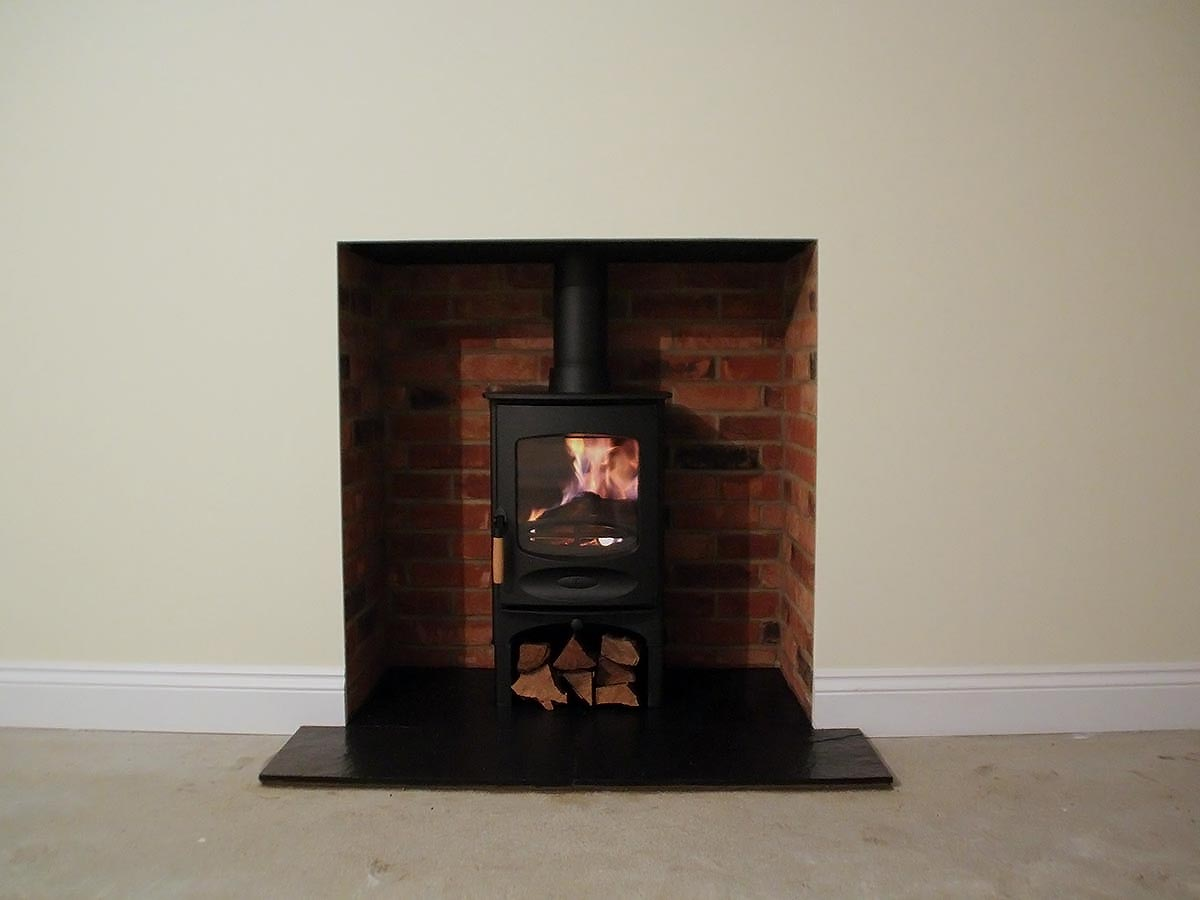 Red brick fireplace with wood stove