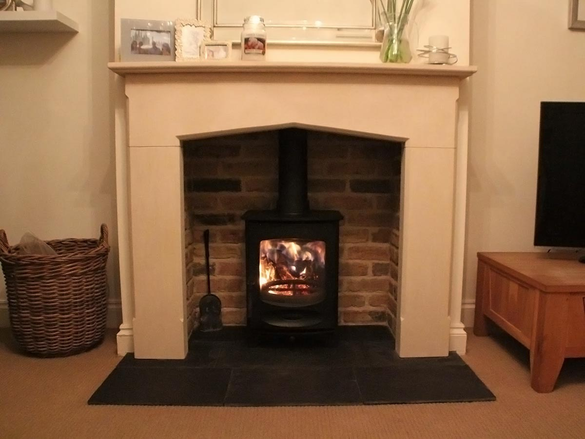 Limestone mantel fireplace with bricks slips