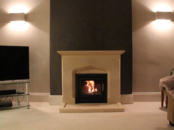 Stovax insert stove installed into limestone fireplace