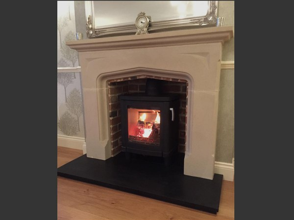 Limestone fireplace mantel with contura 51L side view